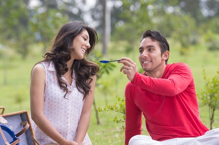 spoiling: handsome young man feeding cute girlfriend at a picnic outdoors
