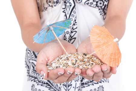 mini umbrella: closeup of girl s hands carrying sand with two mini umrellas on it isolated on white