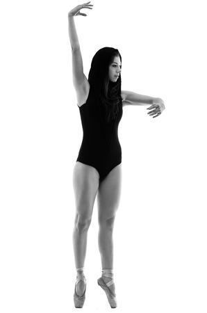 en pointe: Graceful ballerina dancing en pointe fullbody shot isolated on white in black and white