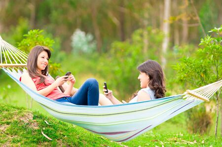 Two happy young girls holding cellphones lying on a hammock  photo