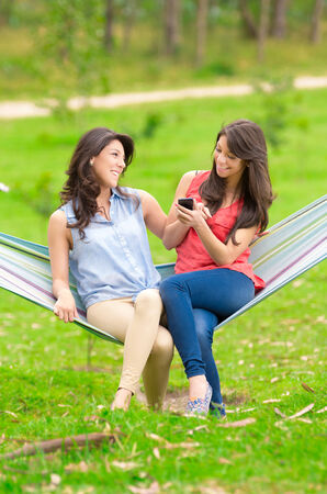 Two young girls sitting on a hammock and smiling with cell phone photo