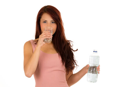 Happy latin young girl holding a bottle and drinking water from glass isolated on white photo
