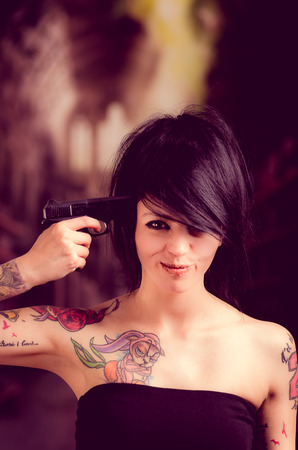 Beautiful tattooed girl with attitude holding gun pointing to her head selective focus Stock Photo