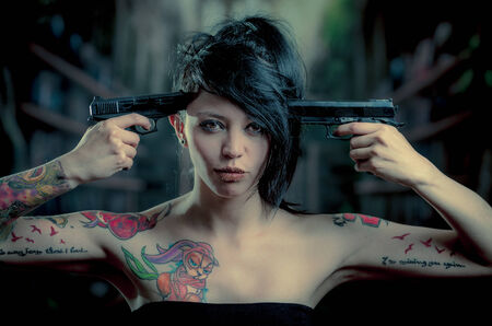 provocative tattooed girl poiting guns to her head looking at camera photo