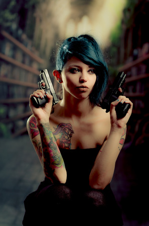 provocative tattooed girl in black dress poiting guns to the sides