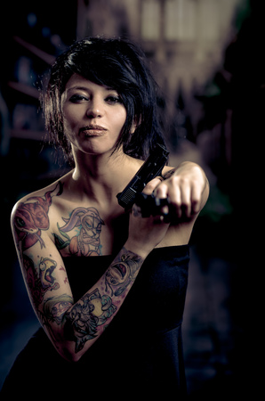 Beautiful tattooed girl in black dress with attitude pointing gun to camera