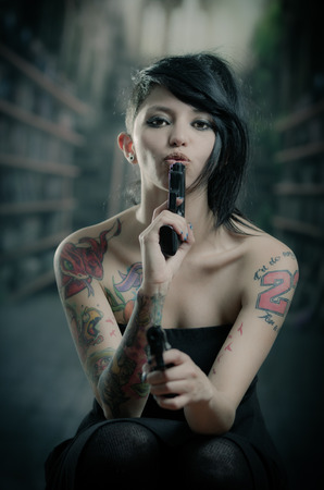 attitude girls: provocative tattooed girl in black dress blowing one gun and pointing front the other one