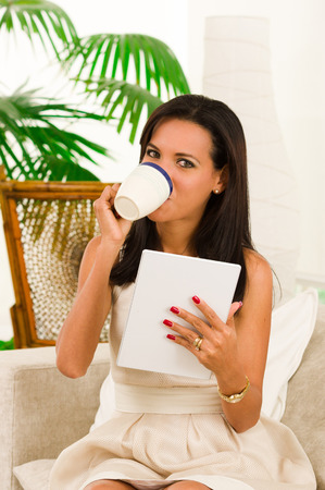 sofisticated: Beautiful young sofisticated happy woman sitting in sofa using tablet and drinking a coffee