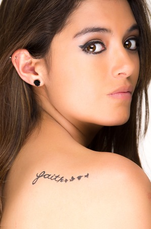 Closeup portrait of beautiful girl with faith tatoo on her back isolated on white photo