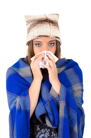 Beautiful young ill latin girl with a cold blowing her nose covered with a blanket isolated on white photo