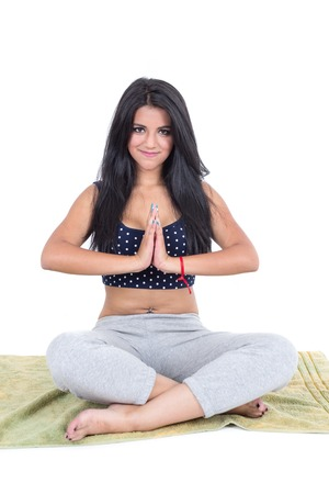 Young brunette girl sitting with crossed legs doing yoga