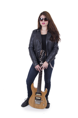 Beautiful rebel young red haired girl posing with electric guitar isolated on white photo