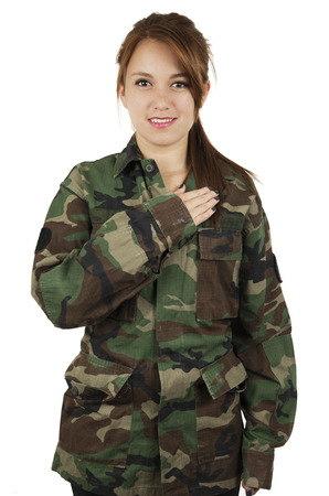 Happy teenage patriotic young girl wearing green military jacket with hand on chest isolated on white photo