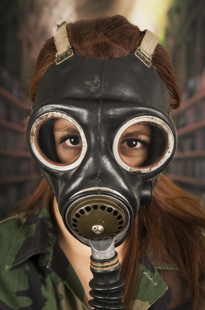 Young girl wearing military uniform and gas mask over dark background photo