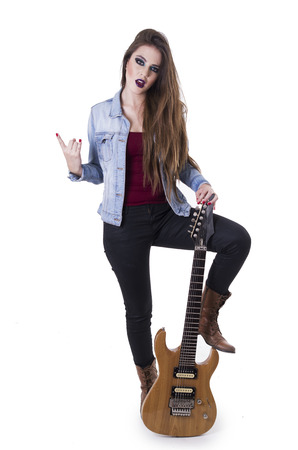Gogeous blond rocker confident girl gesturing rock on holding electric guitar isolated on white