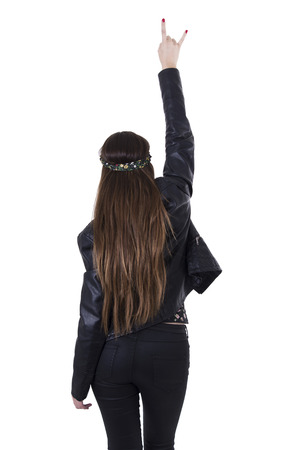 Beautiful young hippie rocker funky fashionable girl holding hand up gesturing rock on rear view isolated on white photo