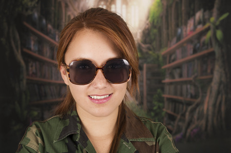 Portrait of young girl wearing military jacket and sunglasses over dark background photo