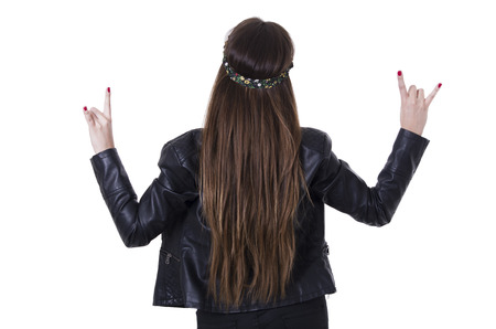 Beautiful young hippie rocker funky fashionable girl gesturing rock on rear view isolated on white photo