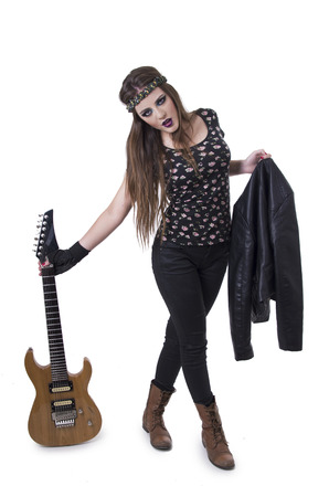 anarchism: Beautiful young rocker girl dressed in black holding electric guitar and jacket isolated on white