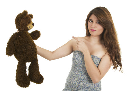 Young beautiful brunette teenage girl pointing disappointed at teddy bear isolated on white photo