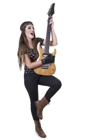 Young pretty happy blond rocker girl playing electric guitar isolated on white photo