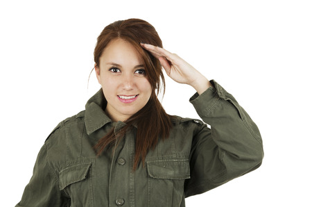 Portrait of beautiful young girl wearing green military style jacket saluting isolated on white photo