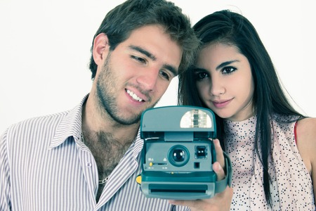 Closeup of cute young hispanic couple taking photos with instant old camera isolated on white photo