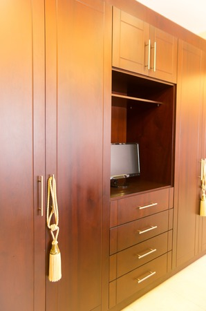 display of beautiful wooden closet with built space for television photo