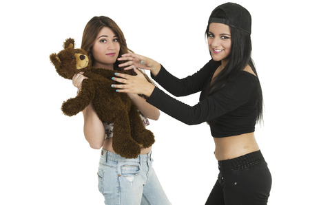 Beautiful young brunette girl ready to strangle teddy bear while friend smiles isolated on white photo