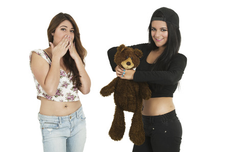 disbelief: Beautiful young happy brunette girl strangling teddy bear while friend watches in disbelief isolated on white