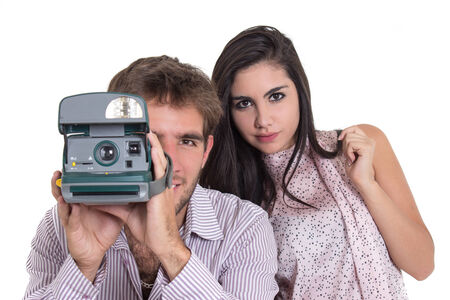 love pic: Closeup of beautiful girl and attractive man using an instant camera isolated on white