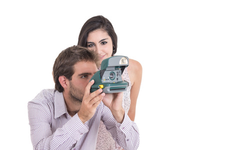 love pic: Beautiful girl and attractive man taking photos with vintage instant camera isolated on white