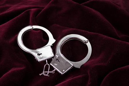 sadistic: Closeup shot of metallic handcuffs on a red velvet textile