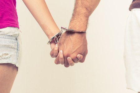 handcuffed: Man and womans hands handcuffed together concept of love, relationship, romance, crime, punishment, prison isolated on white