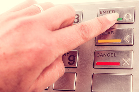 bank withdrawal: Closeup of finger using atm machine with metallic keyboard