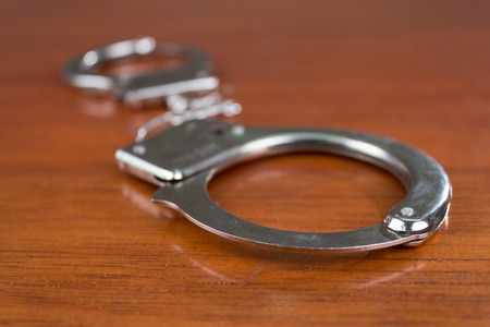 Closeup shot of metallic handcuffs on a table selective focus