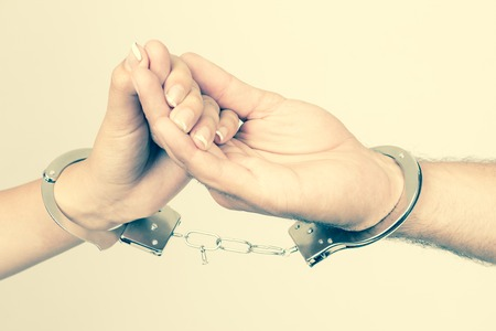 romance sex: Man and womans hands handcuffed together holding hands concept of love relationship romance sex crime punishment prison isolated on white