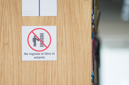 bookshelf in library with do not return book to the shelf sign photo
