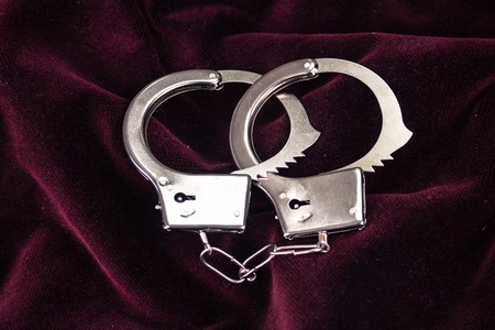Closeup shot of metallic handcuffs on a red velvet textile