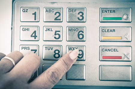 cashpoint: Closeup of finger pressing button in atm machine with metallic keyboard color toned Stock Photo