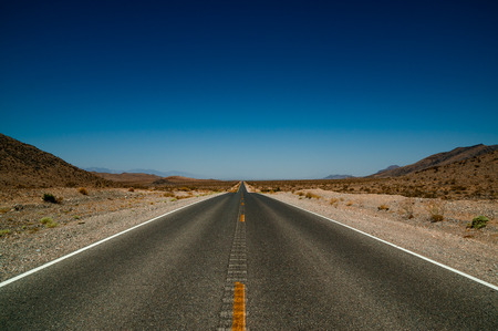 desert road highway with blue sky in background in death valley national park