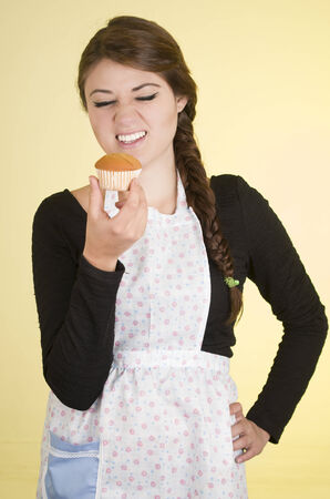 beautiful young woman chef cook baker wearing apron holding muffin looking dissatisfied over yellow background