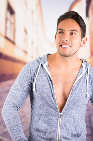 handsome latin man wearing an unzipped hoodie posing over street background photo
