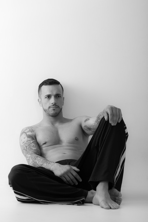 Black and white portrait of Shirtless muscular attractive young man model wearing sweatpants sitting over white background photo