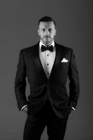 tuxedo jacket: Handsome young latin man wearing a tuxedo black and white portrait