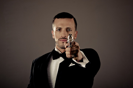 Sexy man gangster agent criminal police in a tuxedo pointing a gun photo