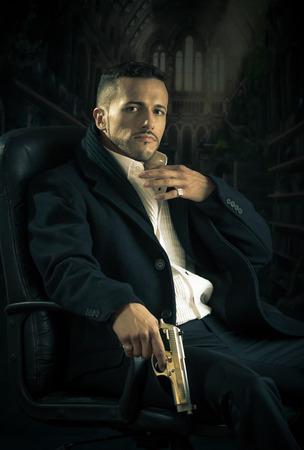 sicario: Elegante y guapo, asesino latino hombre g�ngster esp�a mafia asesino a sueldo que se sienta en una silla con una pistola sobre fondo oscuro Foto de archivo