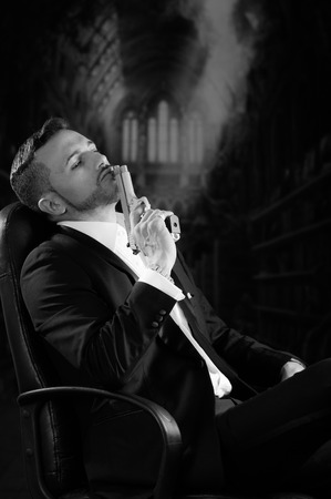 hitman: Sophisticated young man agent police killer hitman assassin sitting and resting gun on his lips over dark background black and white portrait Stock Photo