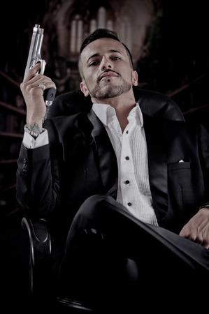 hombre disparando: Joven apuesto hombre espía asesino modelo mafioso asesino a sueldo que se sienta en una silla que señala el arma protagonizando a la cámara
