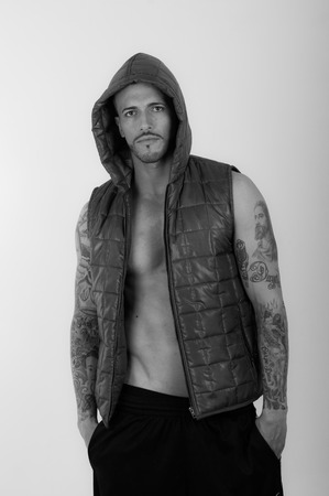Black and white portrait of Young brunette shirtless male model wearing a vest photo